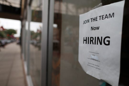 "A ""now hiring"" sign hangs in the window of a Chinese restaurant in downtown Fargo, N.D. Data shows that small businesses are hiring less, despite the strong economy, partly because they are losing employees to bigger firms."