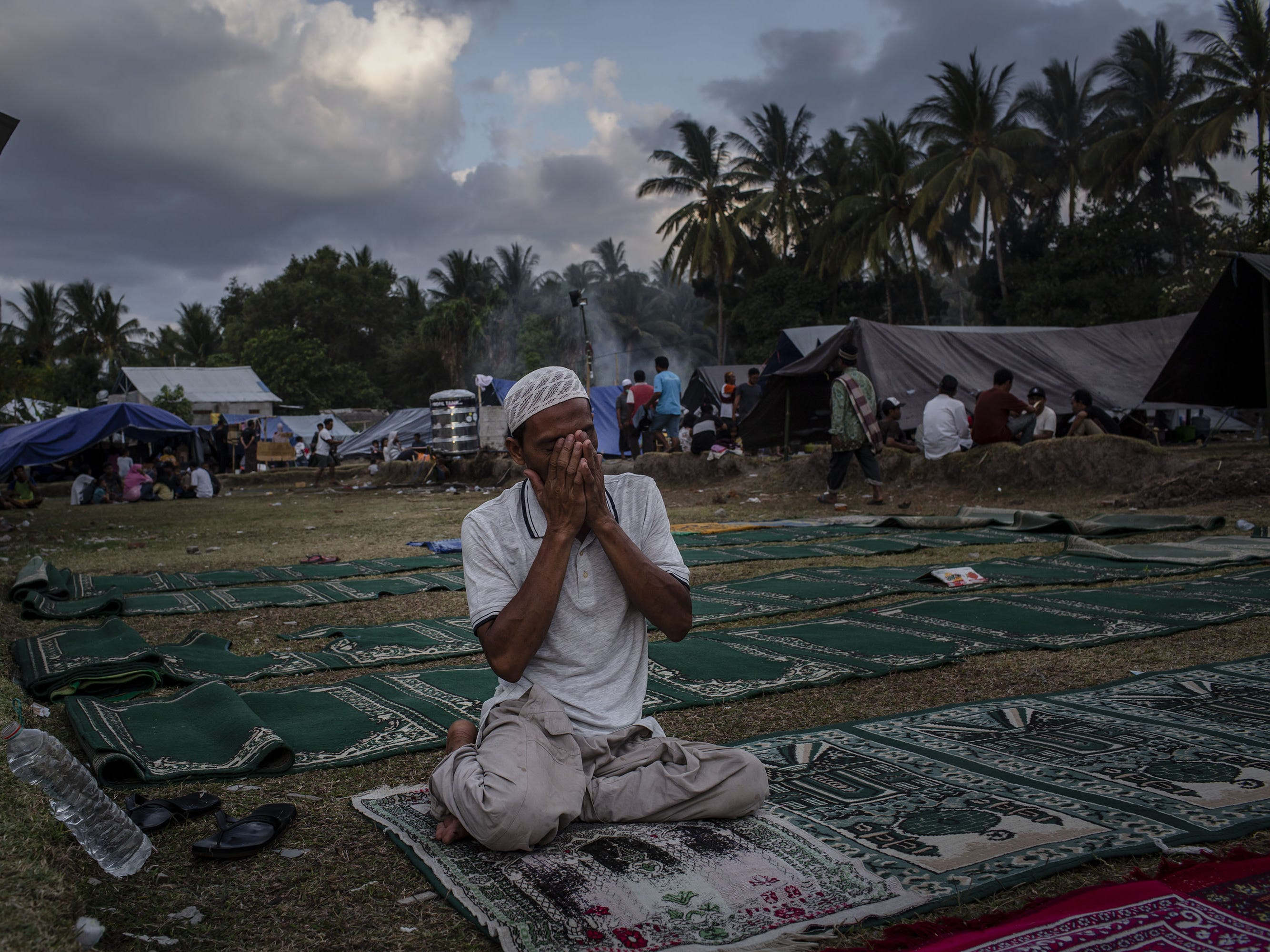 A man prays at a temporary shelter in Pemenang on Aug. 7, 2018 in Lombok Island, Indonesia. Nearly 100 people have been confirmed dead after a 6.9-magnitude earthquake hit the Indonesian island, Lombok, and neighbouring Bali which left at least 20,000 people homeless. Based on reports, officials believe that the death toll may rise with aftershocks expected to rattle the area and aid agencies say their priority is to now provide shelter for displaced people.