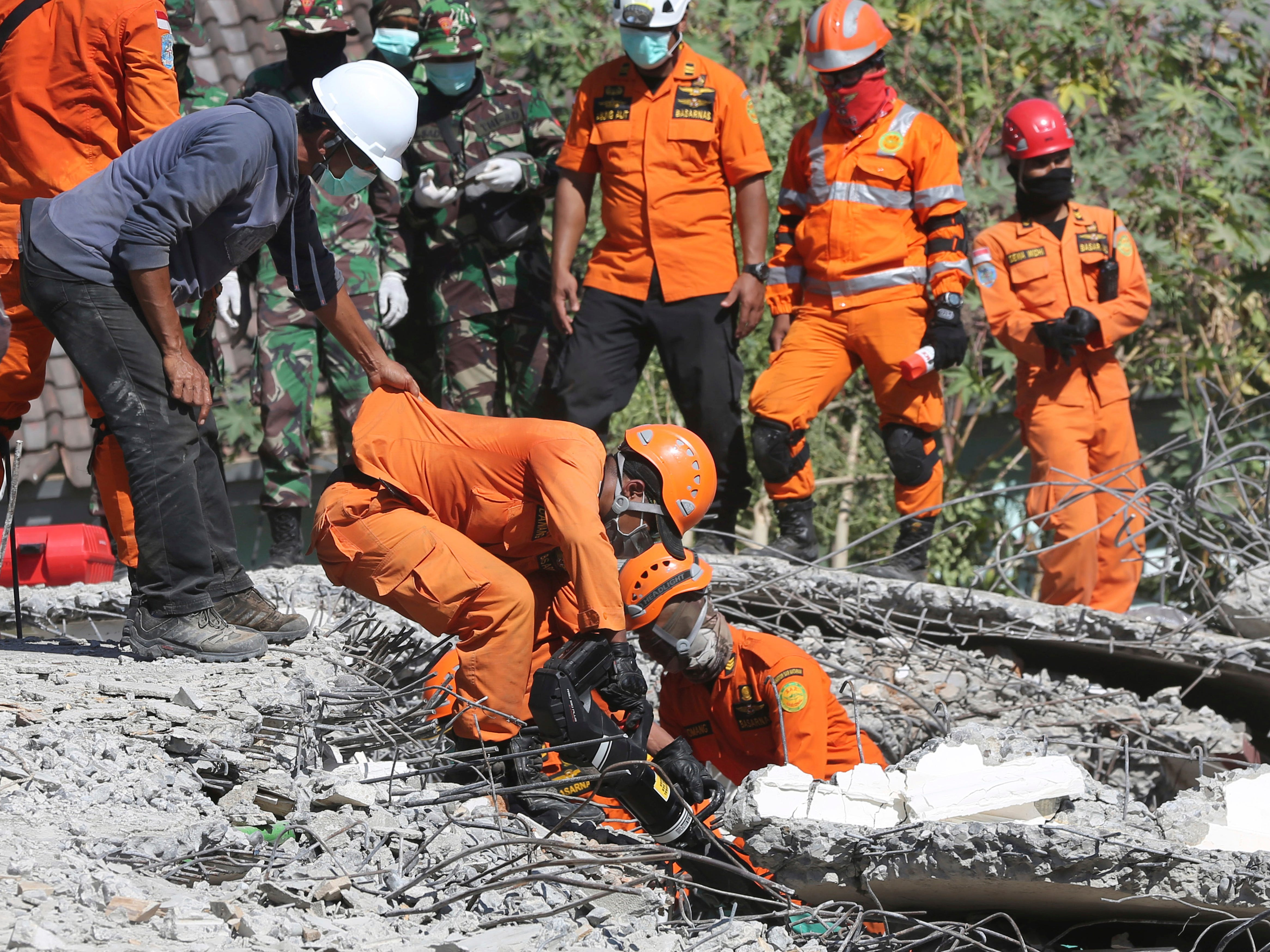 Rescuers carry the body of an earthquake victim recovered from the collapsed Jabal Nur mosque in North Lombok, Indonesia, Tuesday, Aug. 7, 2018. The north of Lombok was devastated by the powerful quake that struck Sunday night, damaging thousands of buildings and killing a large number of people. Rescuers were still struggling to reach all of the affected areas and authorities expect the death toll to rise.