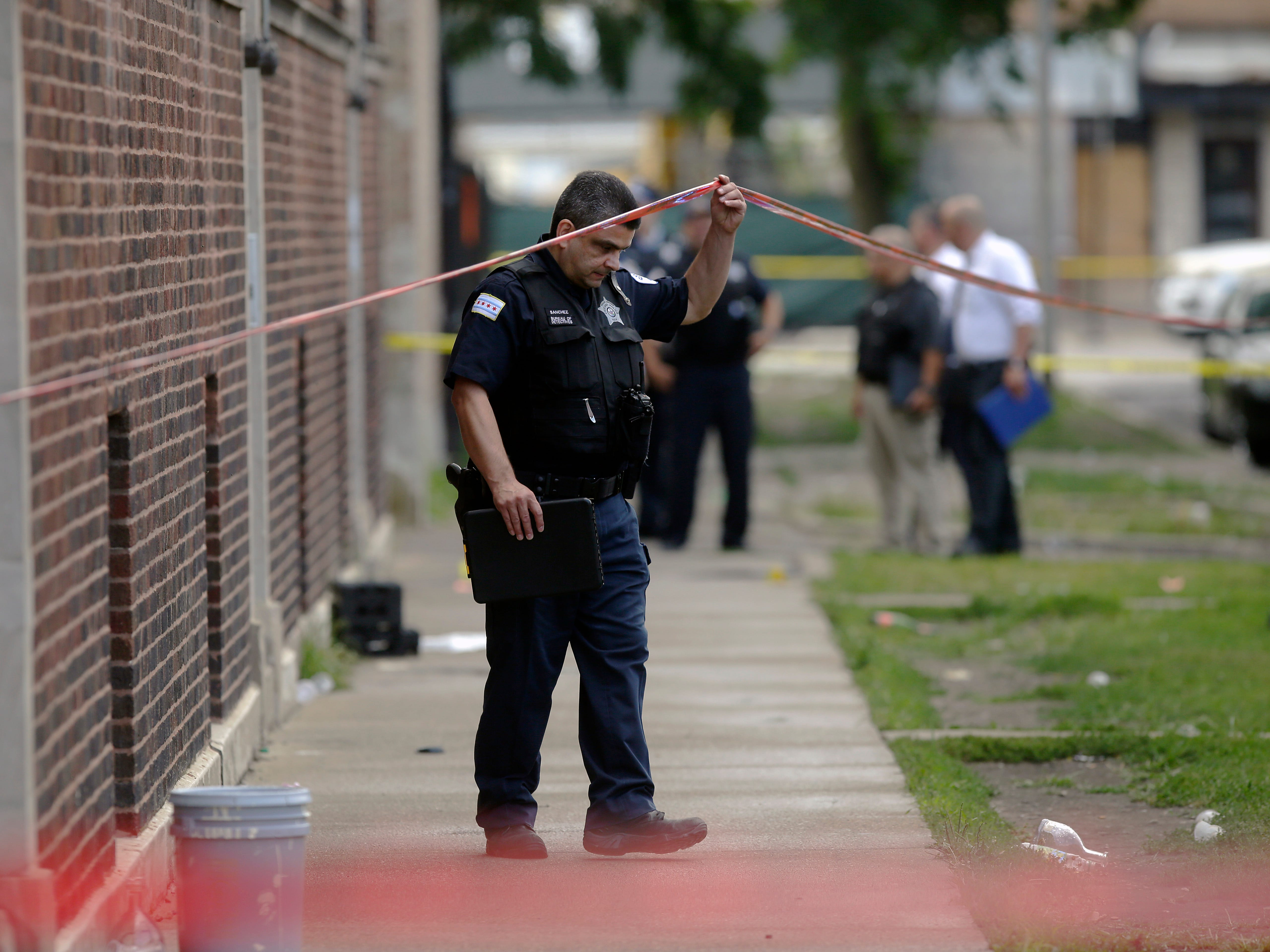 Chicago Police officers and detectives investigate a shooting where multiple people were shot on Sunday, Aug. 5, 2018 in Chicago, IL.