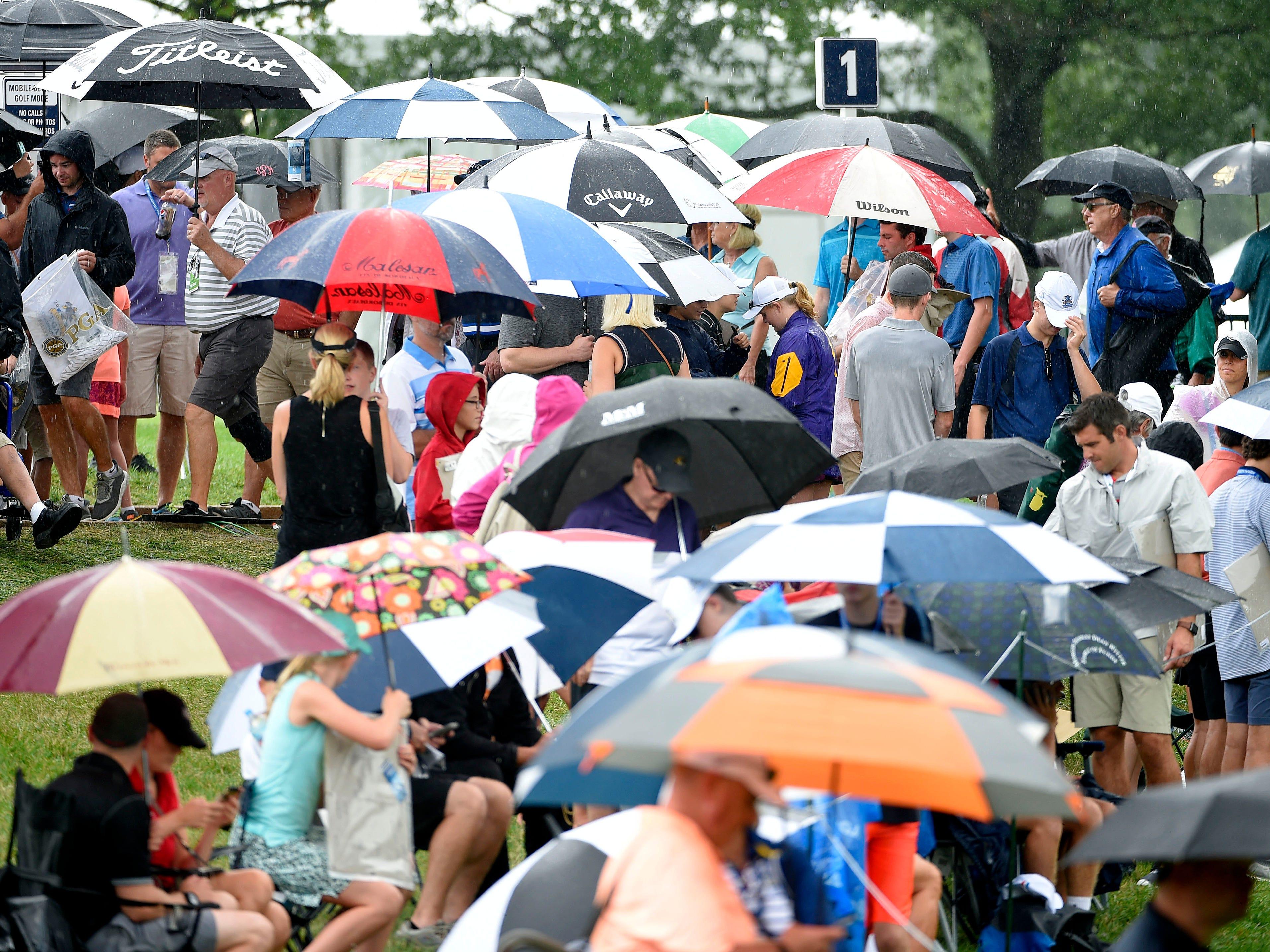Spectators seek shelter during a downpour.