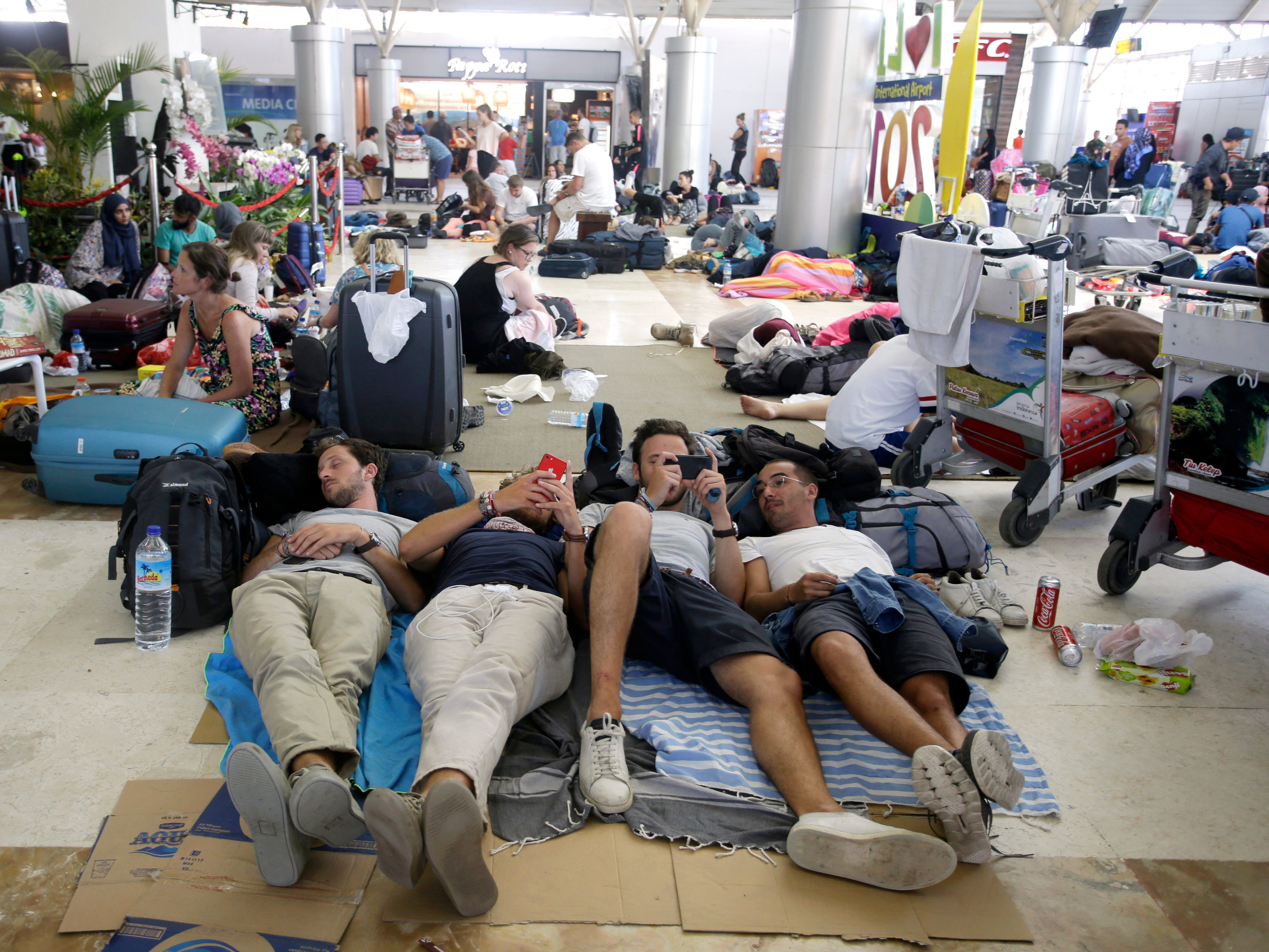 Foreign tourists rest on the floor while waiting for their flights at Lombok International Airport, following an earthquake in Praya, Lombok Island, Indonesia, Tuesday, Aug. 7, 2018.