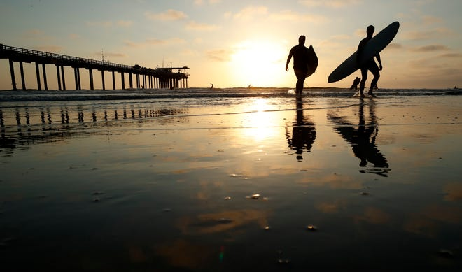 Surfers leave the water next to Scripps Pier Thursday, Aug. 2, 2018, in San Diego. The Scripps Institution of Oceanography says it has recorded the highest sea-surface temperature in San Diego in its 102 years of taking measure.
