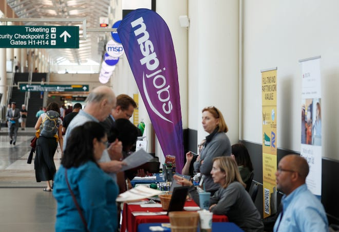 Applicants chat with potential employers during a jobs fair at Minneapolis International Airport in Minneapolis. On Tuesday, Aug. 6, the Labor Department reports on job openings and labor turnover for June.