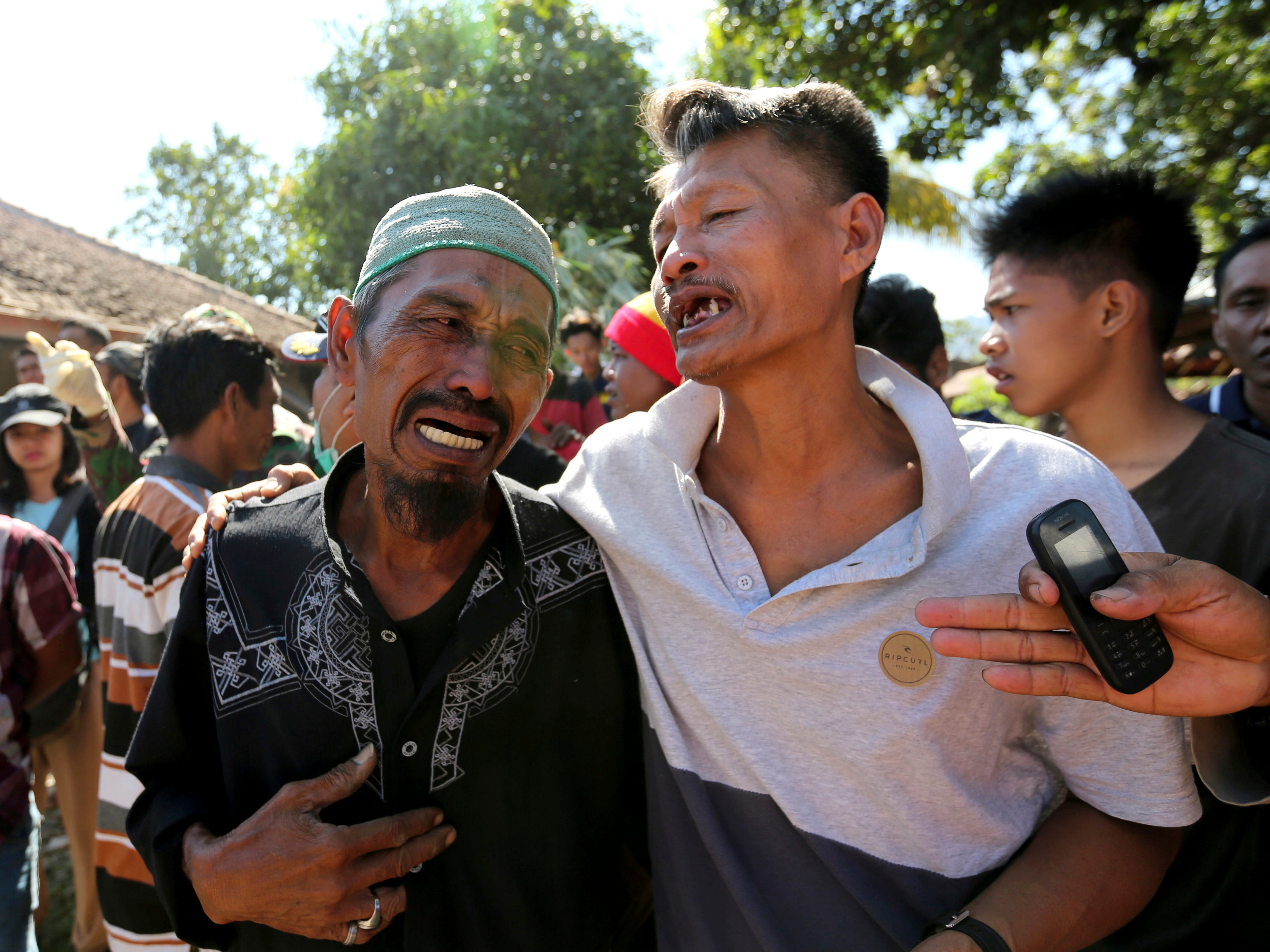 Relatives react as rescue teams recover the bodies of victims killed in an earthquake in North Lombok, Indonesia, Tuesday, Aug. 7, 2018.