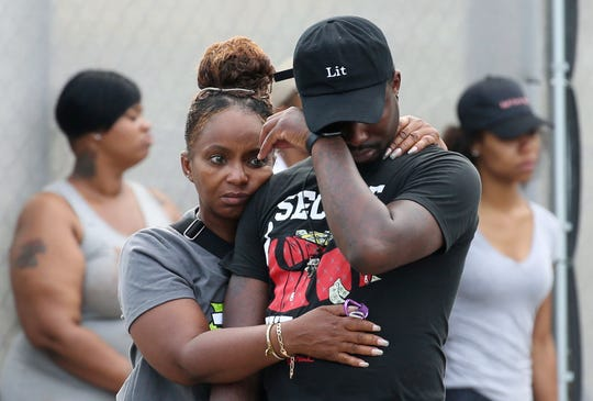 In this Sunday, Aug. 5, 2018 photo, a man wipes his eyes outside the Stroger Hospital in Chicago, after leaving the emergency room due to overwhelming crowds of family and friends of shooting victims.