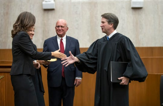 President Donald Trump's Supreme Court nominee, Judge Brett Kavanaugh, right, officiates at the swearing-in of Judge Britt Grant, left, joined by her parents Deborah and Charles Cagle, to take a seat on the U.S. Court of Appeals for the Eleventh Circuit on Aug. 7, 2018, at the U.S. District Courthouse in Washington.