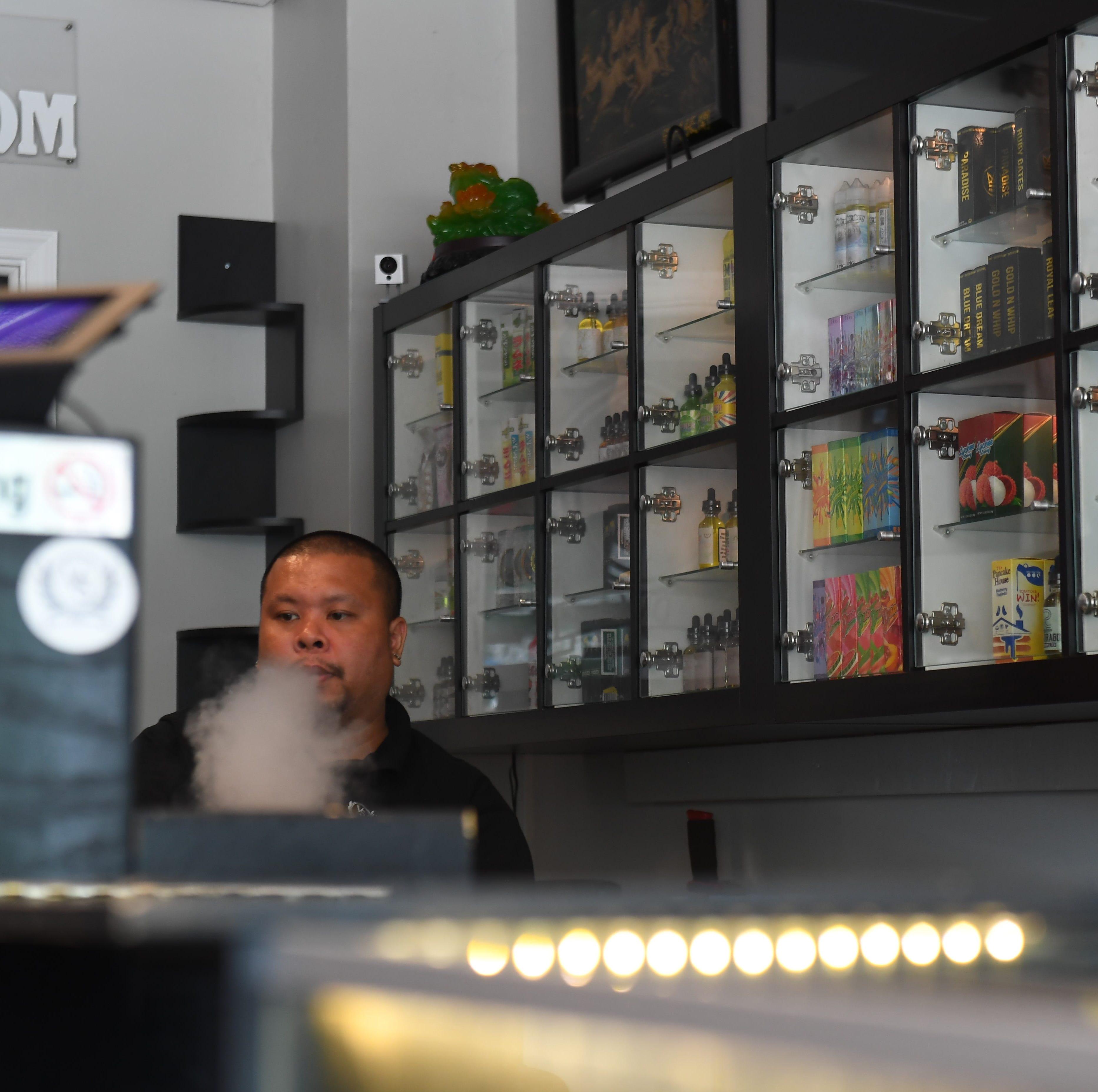 Brandon Nguyen, co founder of Vapor Solutions DMV, is seen vaping at the store in Falls Church, VA.