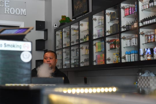 Brandon Nguyen, co founder of Vapor Solutions DMV, is seen vaping at the store in Falls Church, VA.