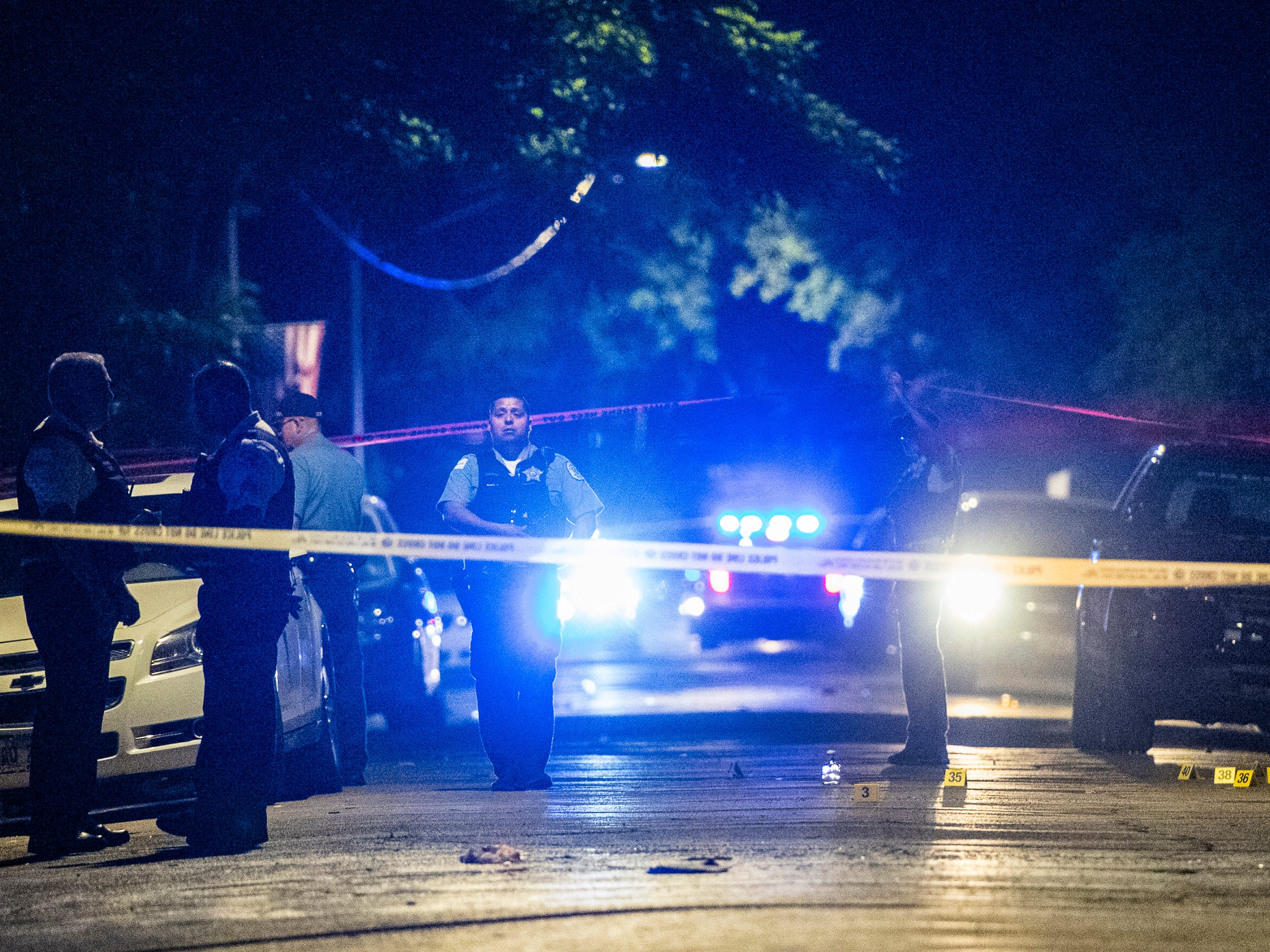 In this Aug. 5, 2018 photo, police investigate the scene where multiple people were shot in Chicago.