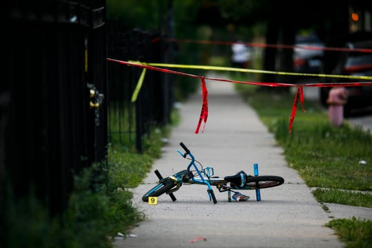 Evidence markers sit on the ground at the scene where a boy was killed after being shot in the abdomen while riding his bike in Chicago.