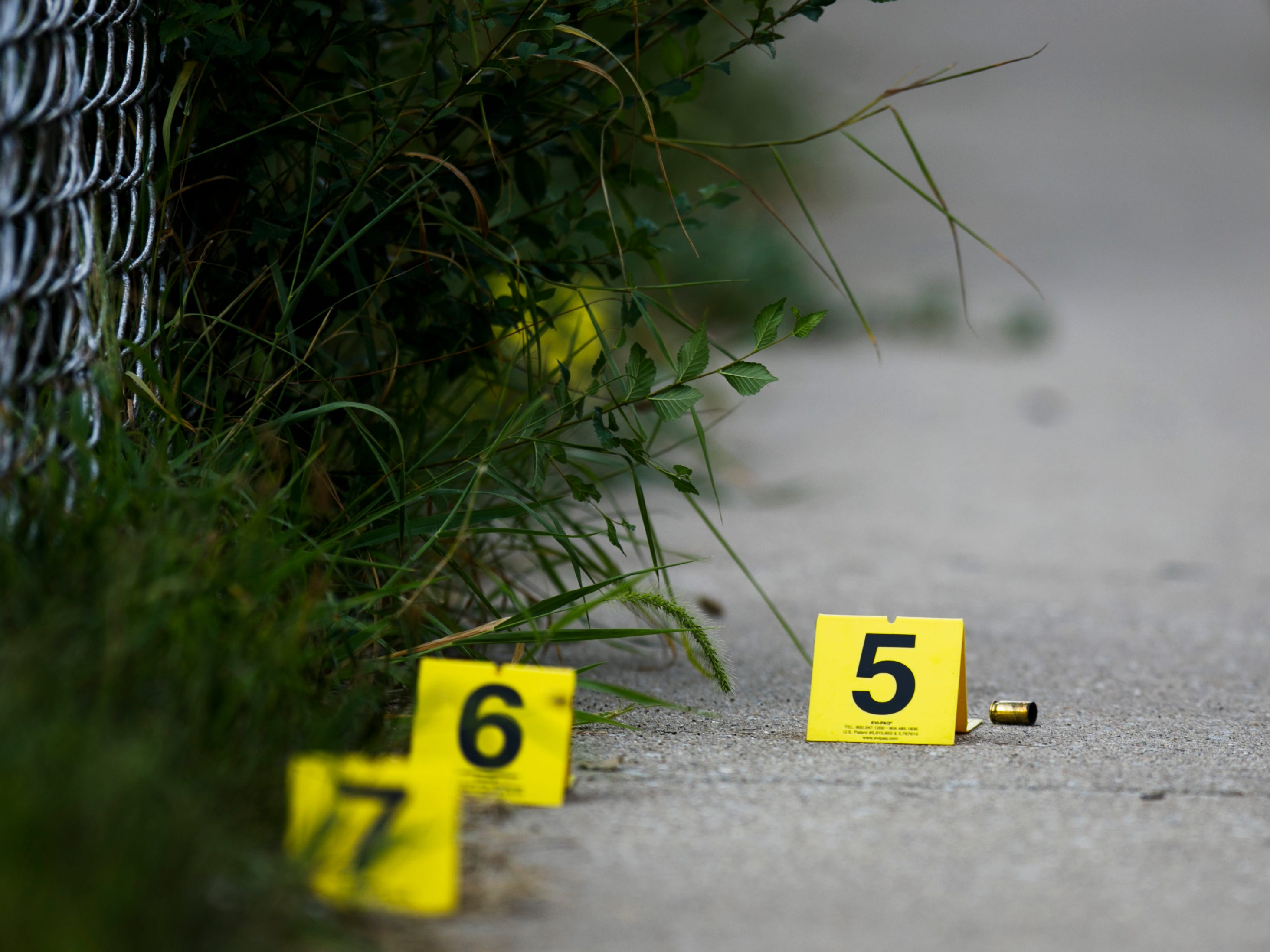 In this Sunday, Aug. 5, 2018 photo, evidence markers sit on the ground at the scene where a boy was killed after being shot in the abdomen while riding his bike in Chicago. Police Superintendent Eddie Johnson plans to discuss the weekend violence during a Monday news conference.