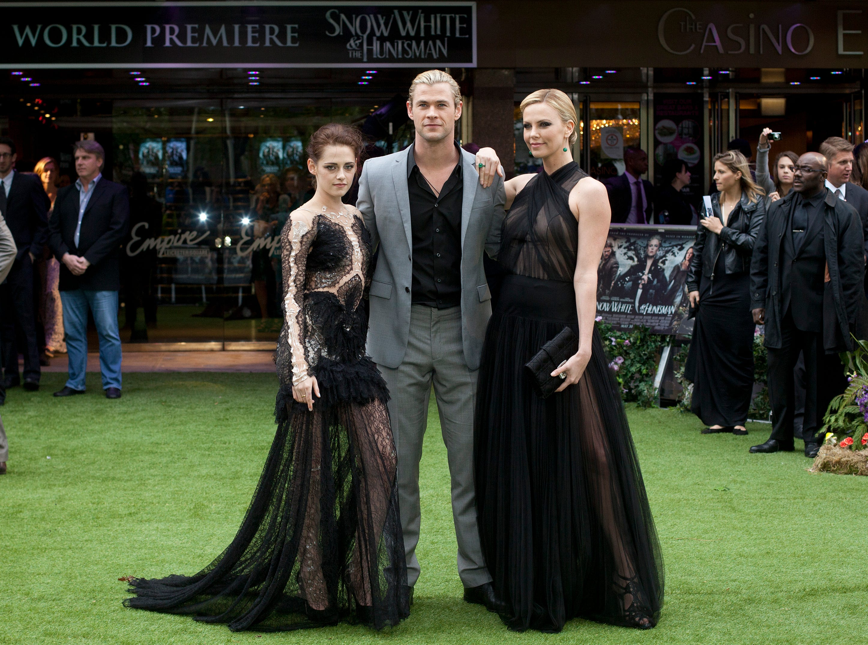 ORG XMIT: XAG113 Actors Kristen Stewart, left, with Charlize Theron, right and Chris Hemsworth pose for the media at the World Premiere of the film Snow White and the Huntsman at a cinema in central London, Monday, May 14, 2012. (AP Photo/Alastair Grant)