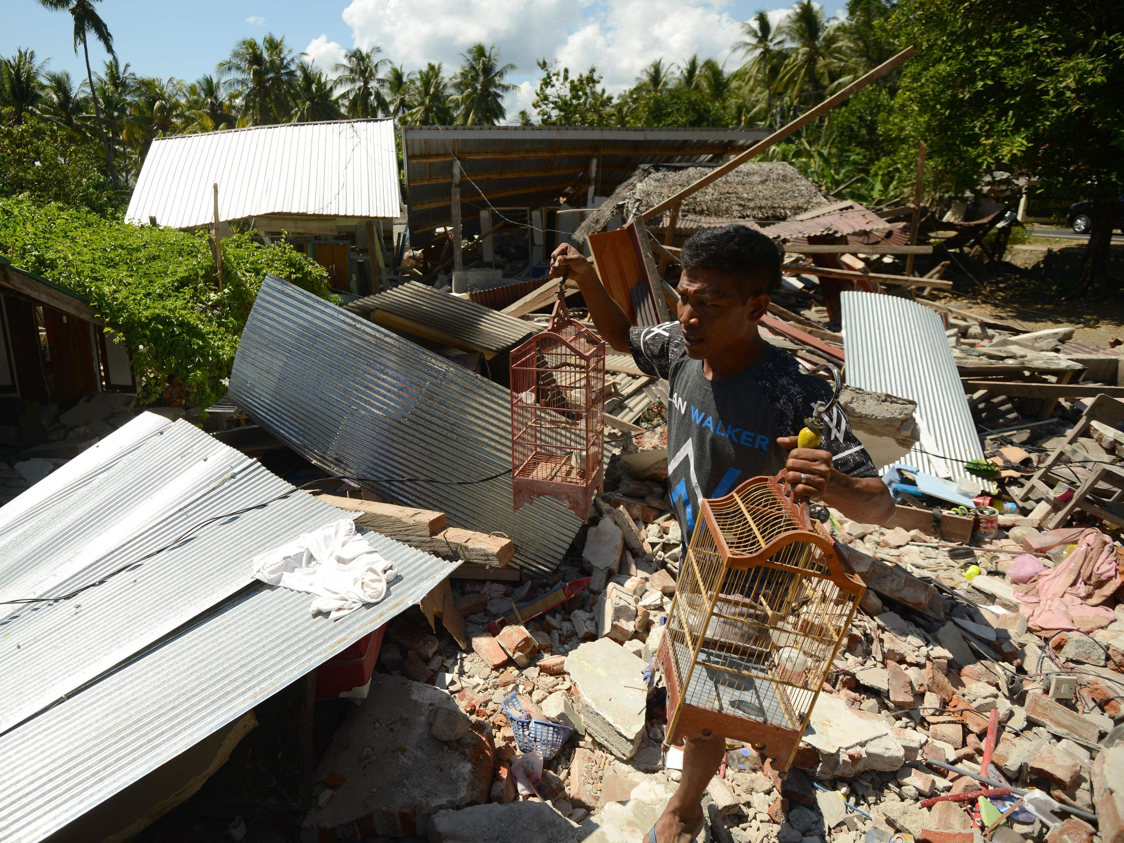 A man carrying bird cages walks past a damaged house at Pemenang village in northern Lombok in West Nusa Tenggara province on Aug. 7, 2018, two days after the area was struck by an earthquake.