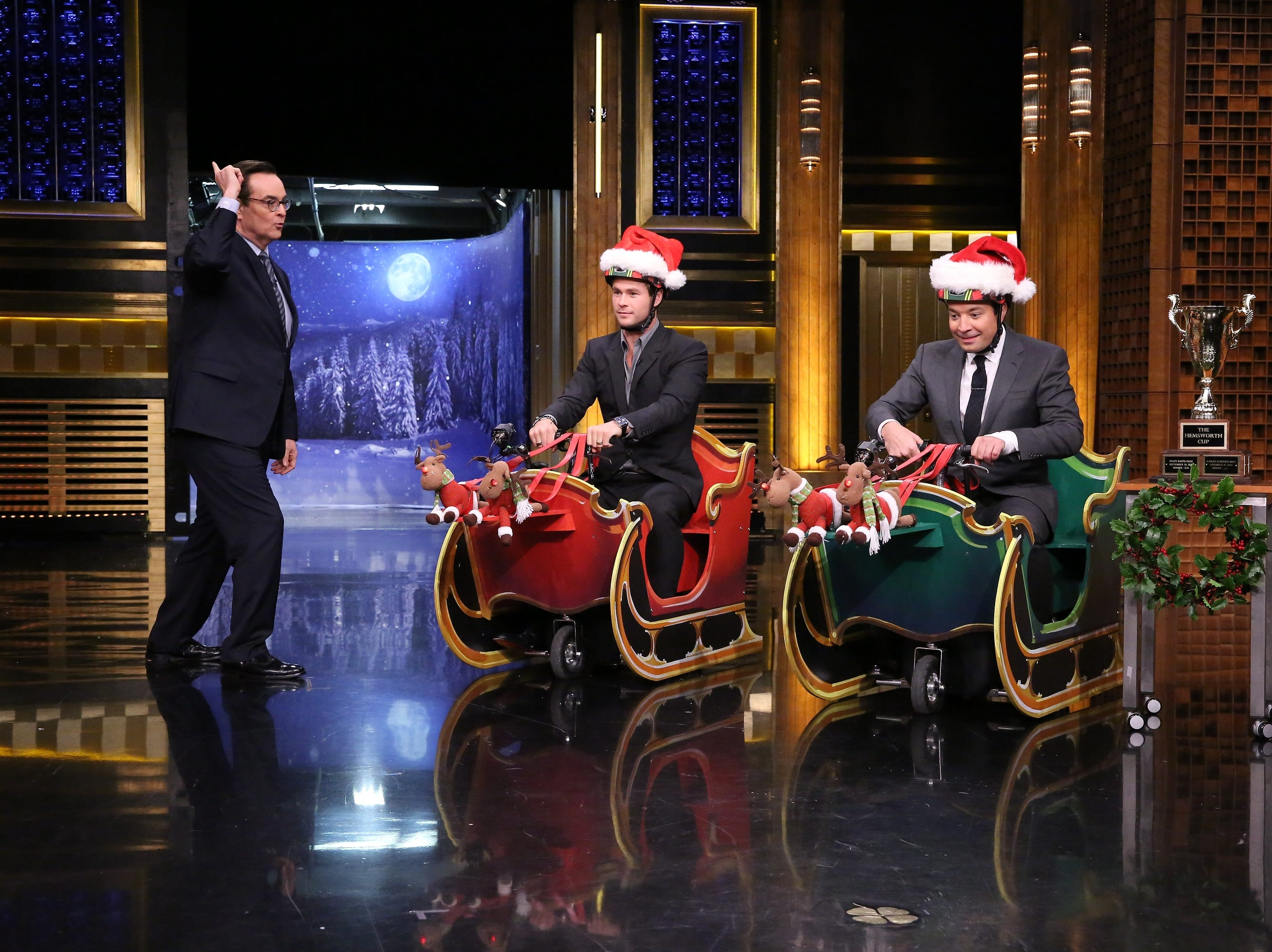 THE TONIGHT SHOW STARRING JIMMY FALLON -- Episode 0385 -- Pictured: (l-r) Announcer Steve Higgins, actor Chris Hemsworth, and host Jimmy Fallon during Cooler Scooter Sleigh Race on December 10, 2015 -- (Photo by: Douglas Gorenstein/NBC) ORG XMIT: Season: 3 [Via MerlinFTP Drop]