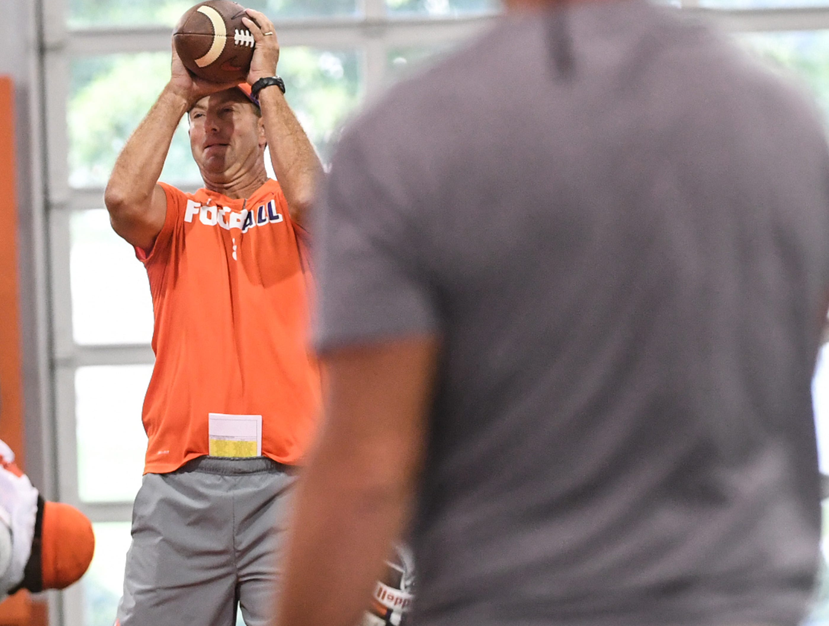 Clemson head coach Dabo Swinney catches a pass from NFL Hall of Fame quarterback Brett Favre during fall practice in Clemson on Wednesday.