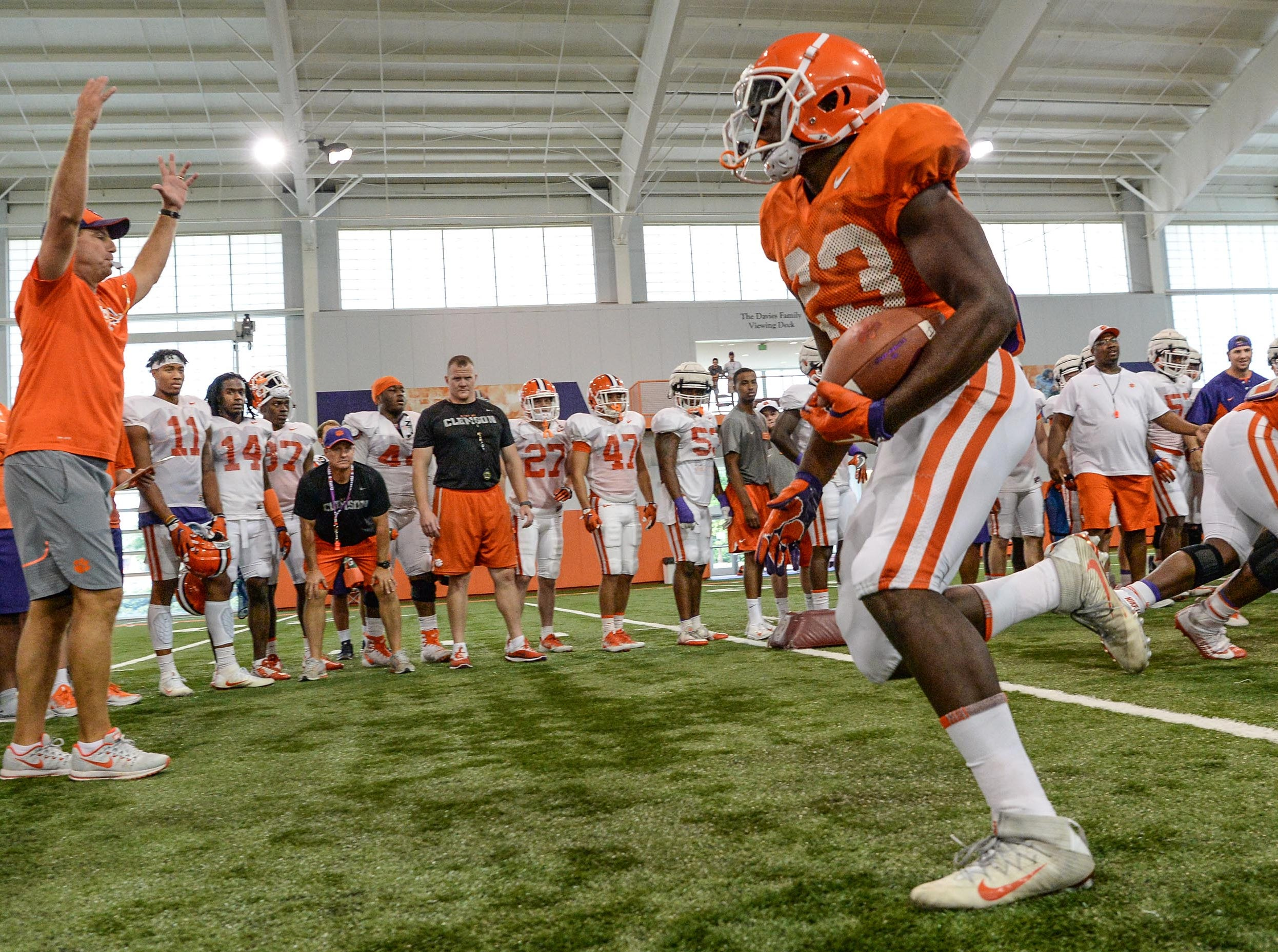 Clemson running back Lyn-J Dixon (23) runs by defenders during fall practice in Clemson on Wednesday.