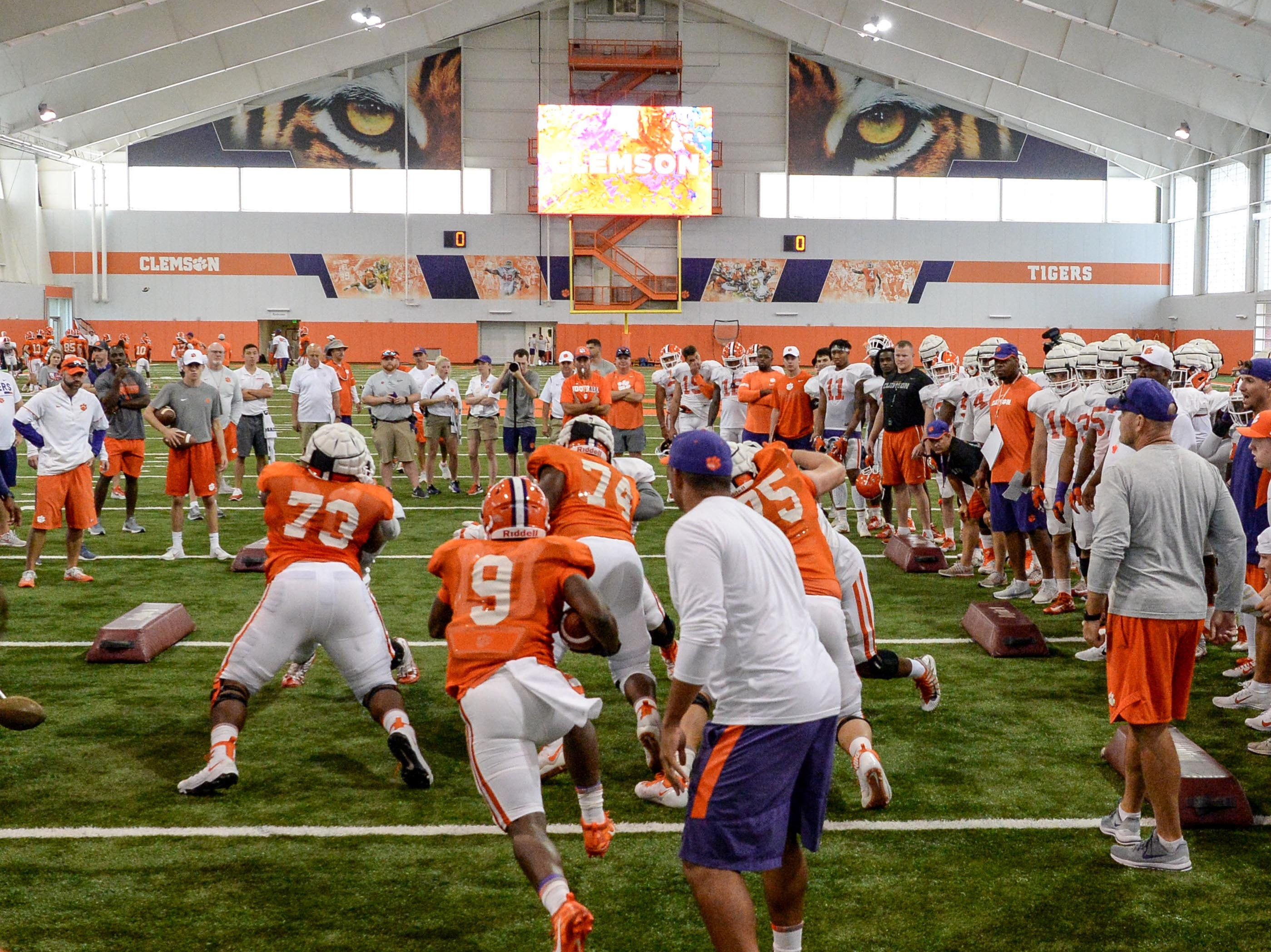 Clemson running back Travis Etienne (9) runs into defenders during fall practice in Clemson on Wednesday.
