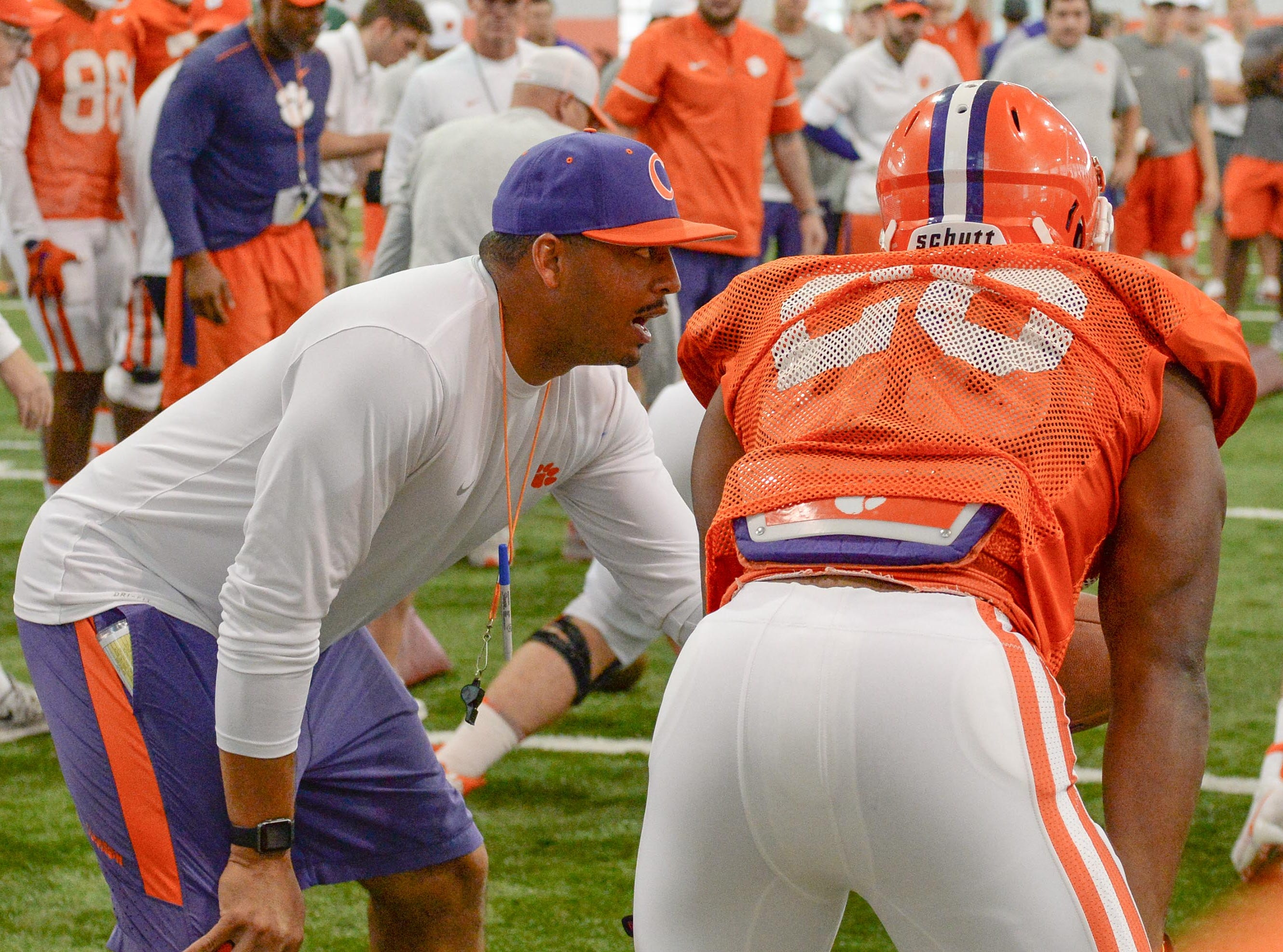co-offensive coordinator Tony Elliott talks to running back Tavien Feaster (28) during fall practice in Clemson on Wednesday.