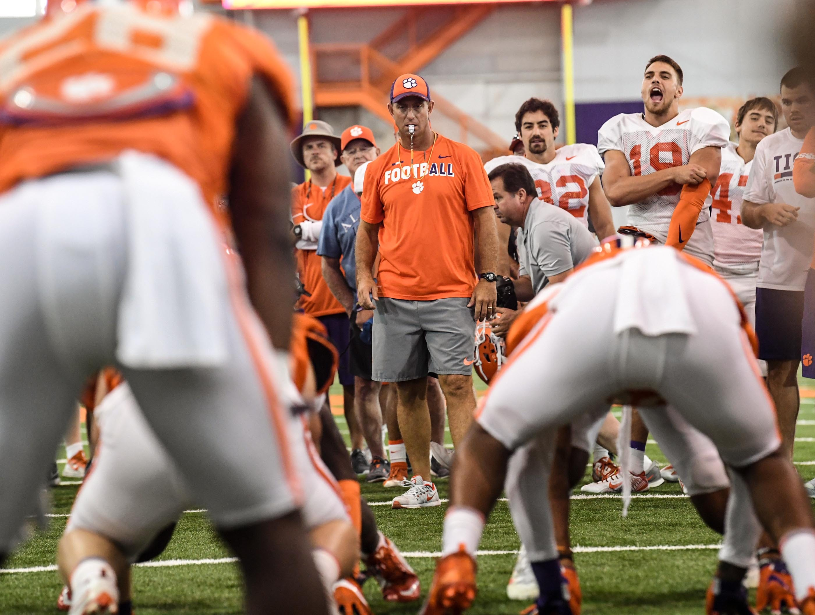 Clemson head coach Dabo Swinney watches Clemson running back Tavien Feaster (28) line up to run through a defense during fall practice in Clemson on Wednesday.