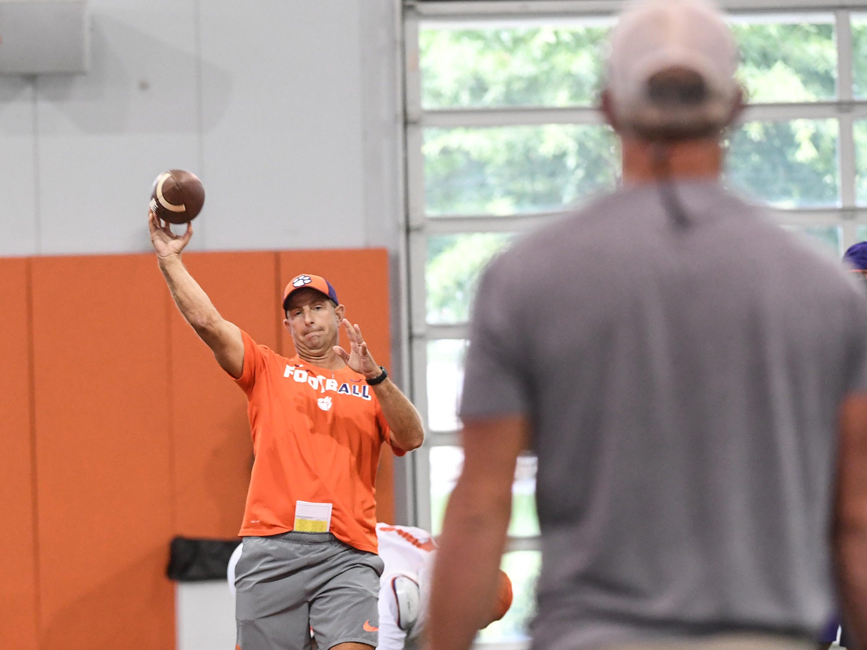 Clemson head coach Dabo Swinney throws a ball to NFL Hall of Fame Class of 2016 quarterback Brett Favre during fall practice in Clemson on Wednesday.