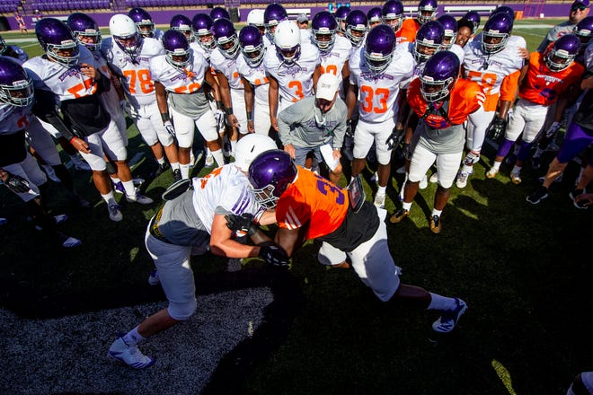 Northwestern State head coach Brad Laird (center) watches closely as defensive end Jordan Greenlee and tight end Charles Vaughn III battle in the Circle of Champions competition to start Tuesday's practice, the Demons' first in full gear this month.