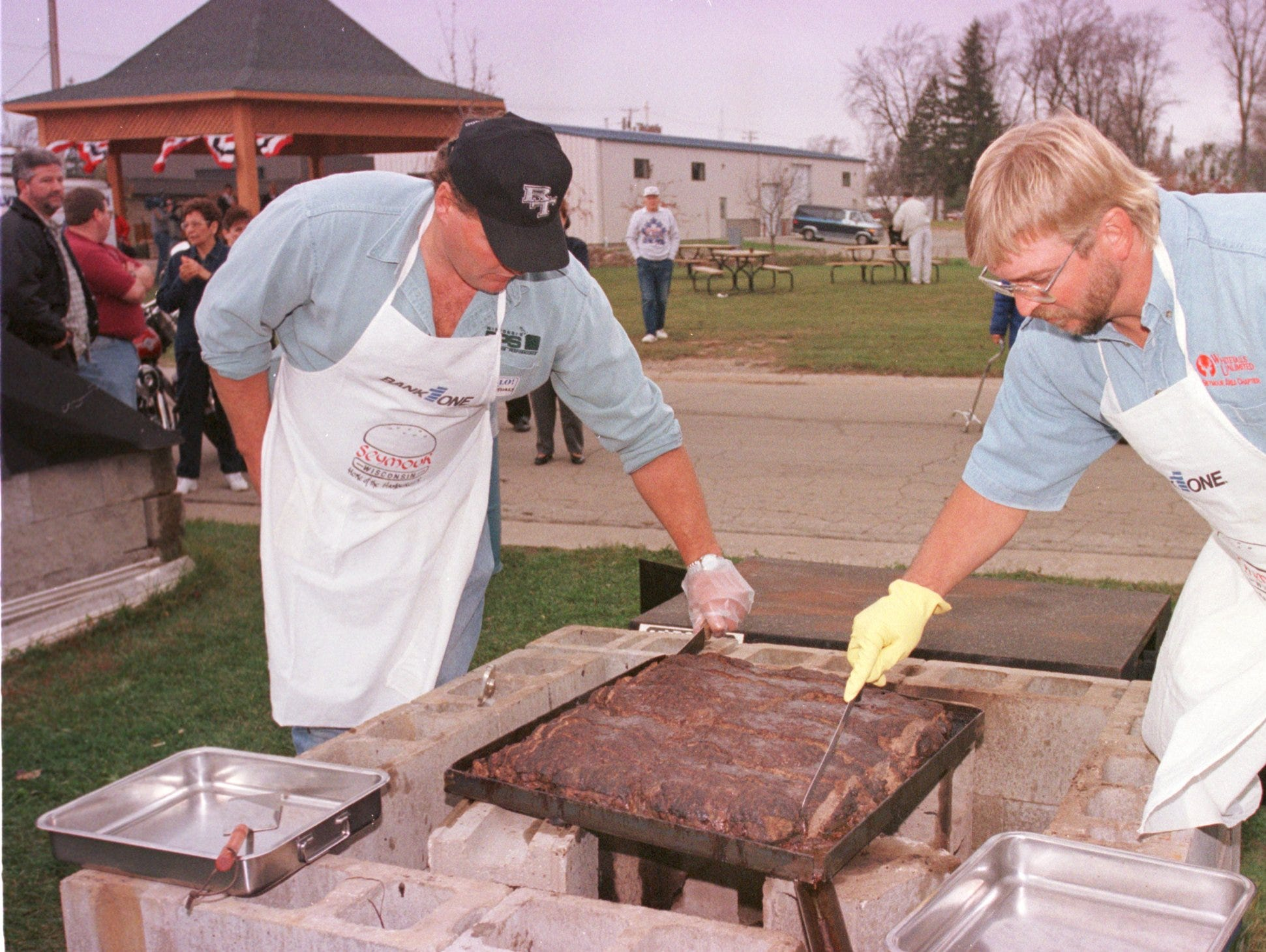 2000: Jerry Maass, left, and Greg Matuszak slice the 50-pound cajun burger they cooked Friday at the Seymour Hamburger Hall of Fame on Depot Street.
