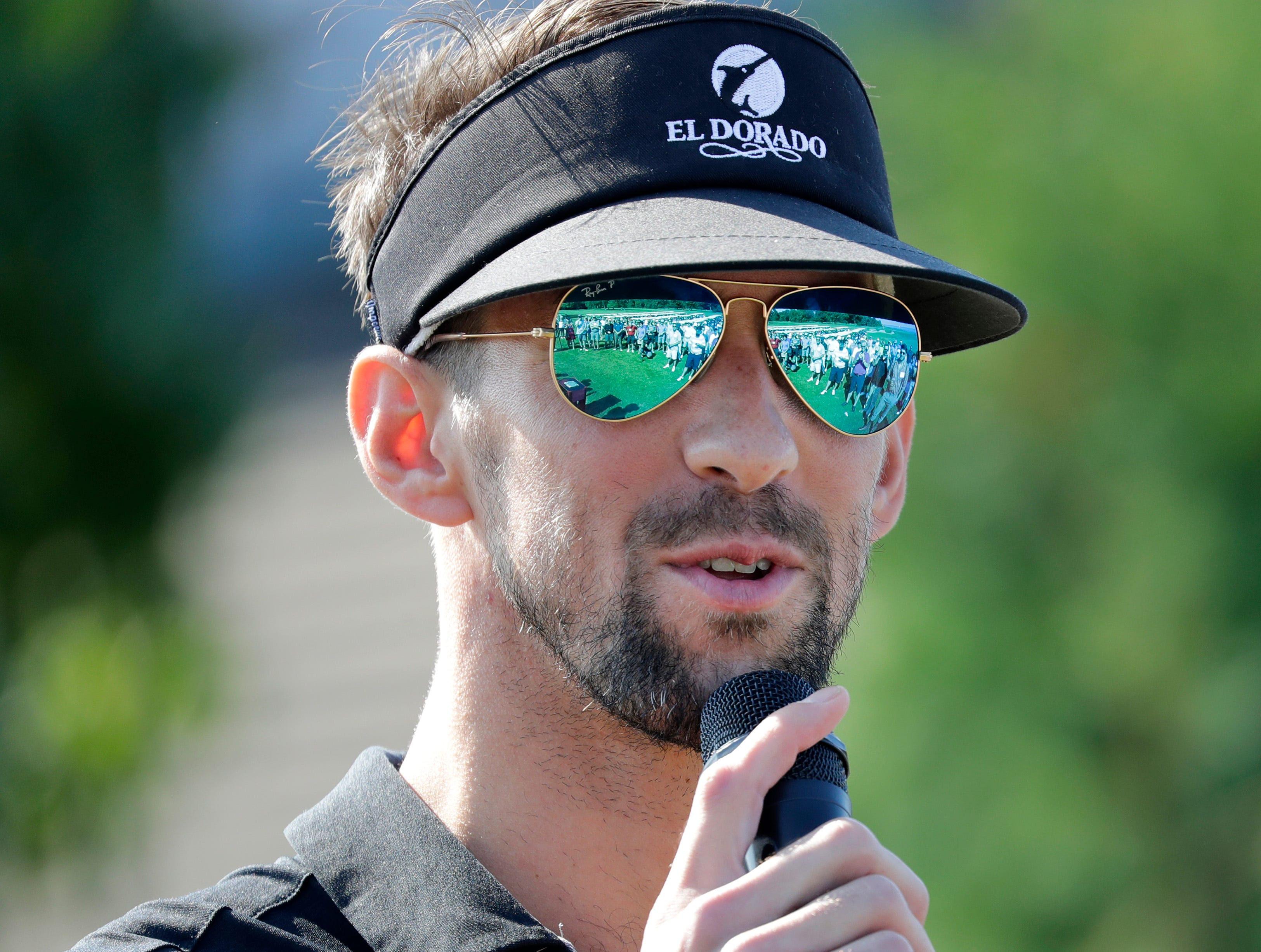 Michael Phelps gives the opening remarks before the start of the U.S. Venture Open Wednesday, Aug. 8, 2018, at North Shore Golf Club in Menasha, Wis.