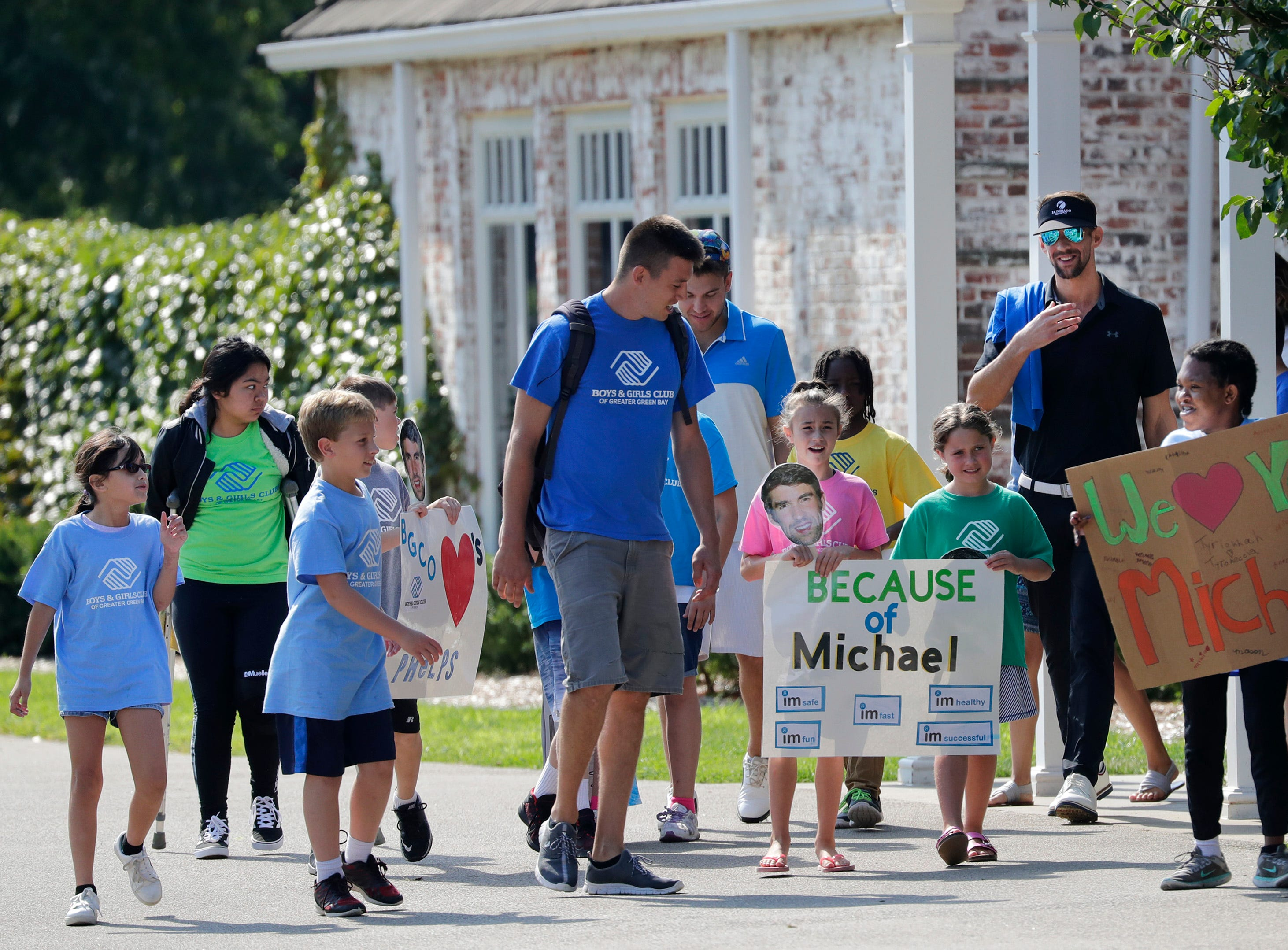 Michael Phelps, right, walks out with members of the Boys and Girls Club before the start of the U.S. Venture Open Wednesday, Aug. 8, 2018, at North Shore Golf Club in Menasha, Wis.