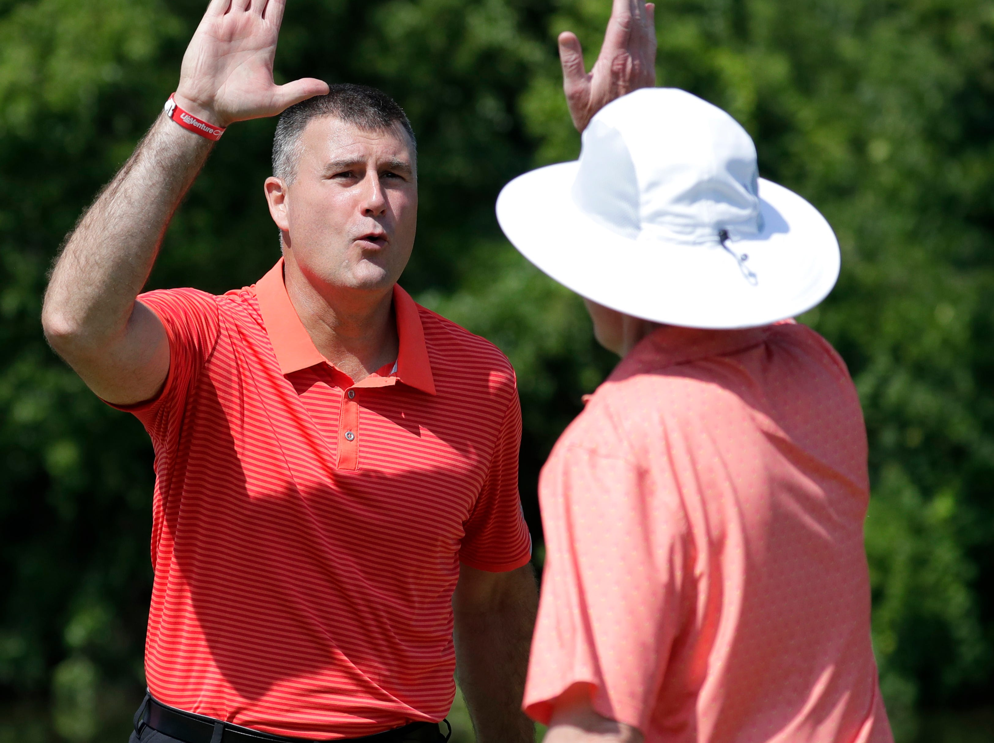 Bill Bohn, left, high fives Pat Hickey, both with Associated Bank, after Hicky sank a putt during the U.S. Venture Open Wednesday, Aug. 8, 2018, at North Shore Golf Club in Menasha, Wis.Danny Damiani/USA TODAY NETWORK-Wisconsin