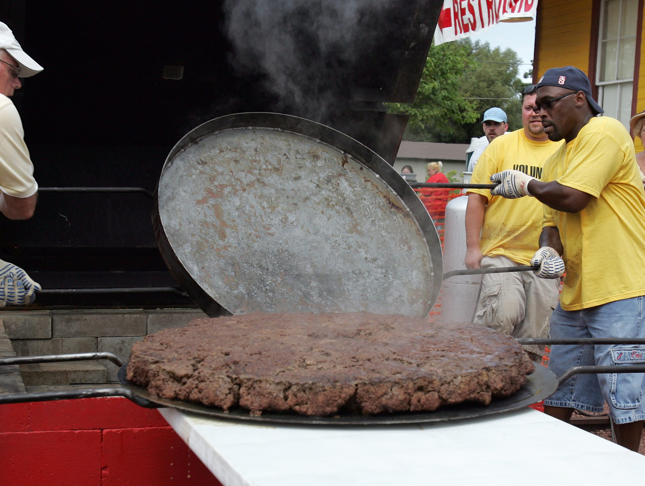 Jim Campbell (left) of Seymour and Elston Taylor of Pulaski work with the 150 pound hamburger during the 2012 Annual Hamburger Festival in Seymour, Wisconsin on Saturday, August 4, 2012. Get Cheezy with Hamburger Charlie was the theme as the 150 pound hamburger was topped with cheese this year.