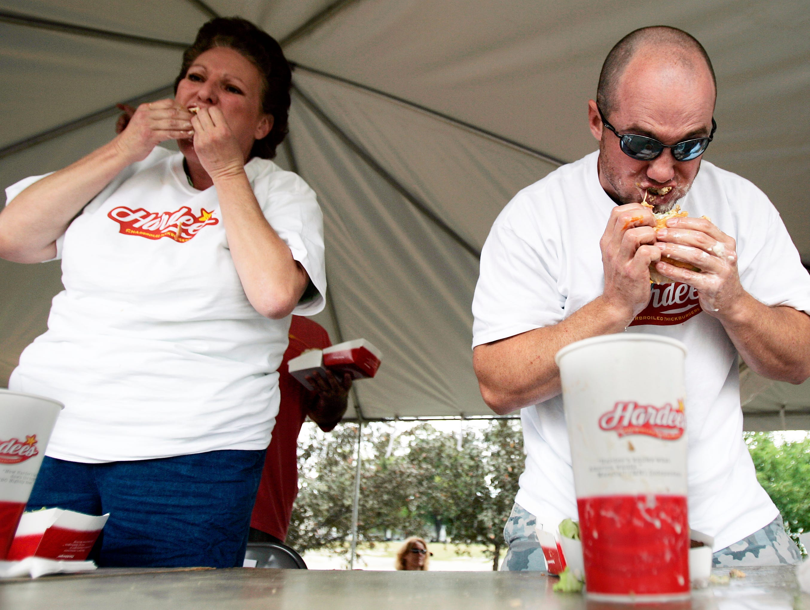 "Betty Morgan of Seymour, left, and Mike ""The Hammer"" Fitzgerald of Menasha, right, bite into their burgers during the Hardee's Hamburger Eating Contest during the 20th Annual Burger Fest in Seymour, Wis., Saturday, Aug. 9, 2008. Morgan was the only female competitor. Fitzgerald set a new event record by eating seven and one-third Hardee's Thickburgers in under 12 minutes. Post-Crescent photo by M.P. King."
