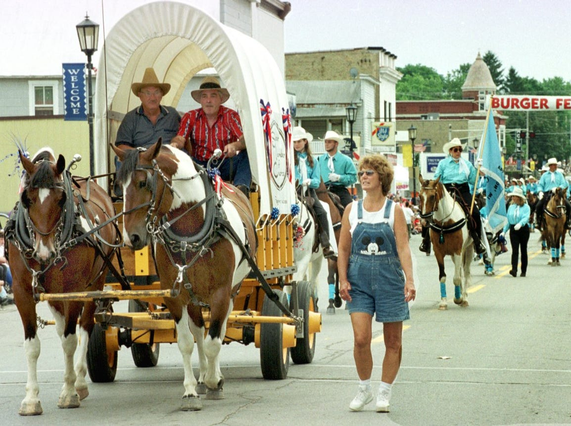 2000: The Seymour Chamber of Commerce's horse-drawn wagon parade entrant rolls through the downtown as onlookers sit along the curb for Saturday's parade.