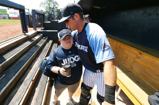 Third year Thunder bat boy Tommy Smith,  gets a hug from catcher Ryan Lidge during a game Wednesday against the Altoona Curve at ARM & HAMMER Park. Smith joined up with the Thunder thanks to a connection between his father, Tom, and Thunder General Manager and Chief Operating Officer  Jeff Hurley.  August 8, 2017, Trenton, NJ.