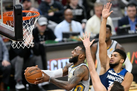 Cleveland Cavaliers forward LeBron James (23) drives between Minnesota Timberwolves center Karl-Anthony Towns (32)