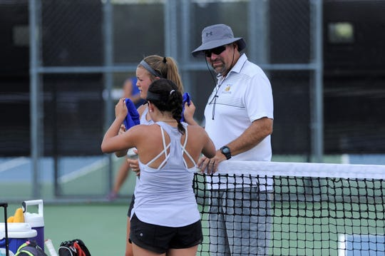 First-year Wylie tennis coach Mark Hathorn talks with Leighton Alford and Analeah Elias during their girls doubles match against Midlothian. Hathorn took over the program after spending the last 17 years at McMurry. Hathorn's three daughters all played tennis at Wylie.