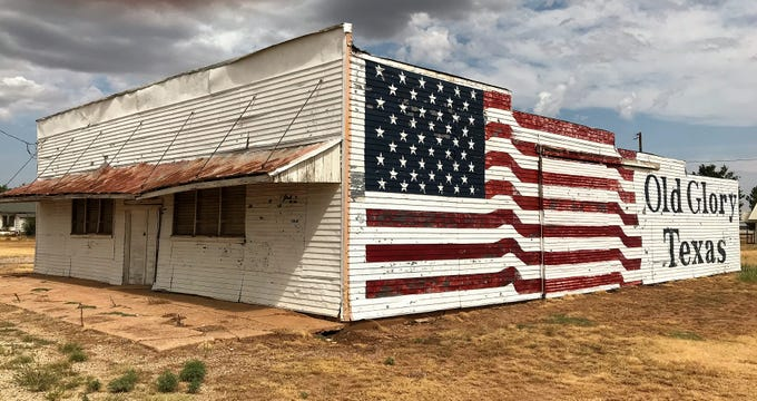 A flag is painted on the side of a vacant building in Old Glory.