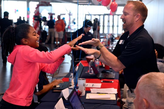 Jayda Mays, 10, plays a hand-clap game with Matt Briggs while waiting for her mother, Kayla, to finish enrolling at the new Texas State Technical College Abilene campus Wednesday. It was the first day of enrollment at the facility, where Briggs answered questions for prospective students about TSTC's emergency medical services program.