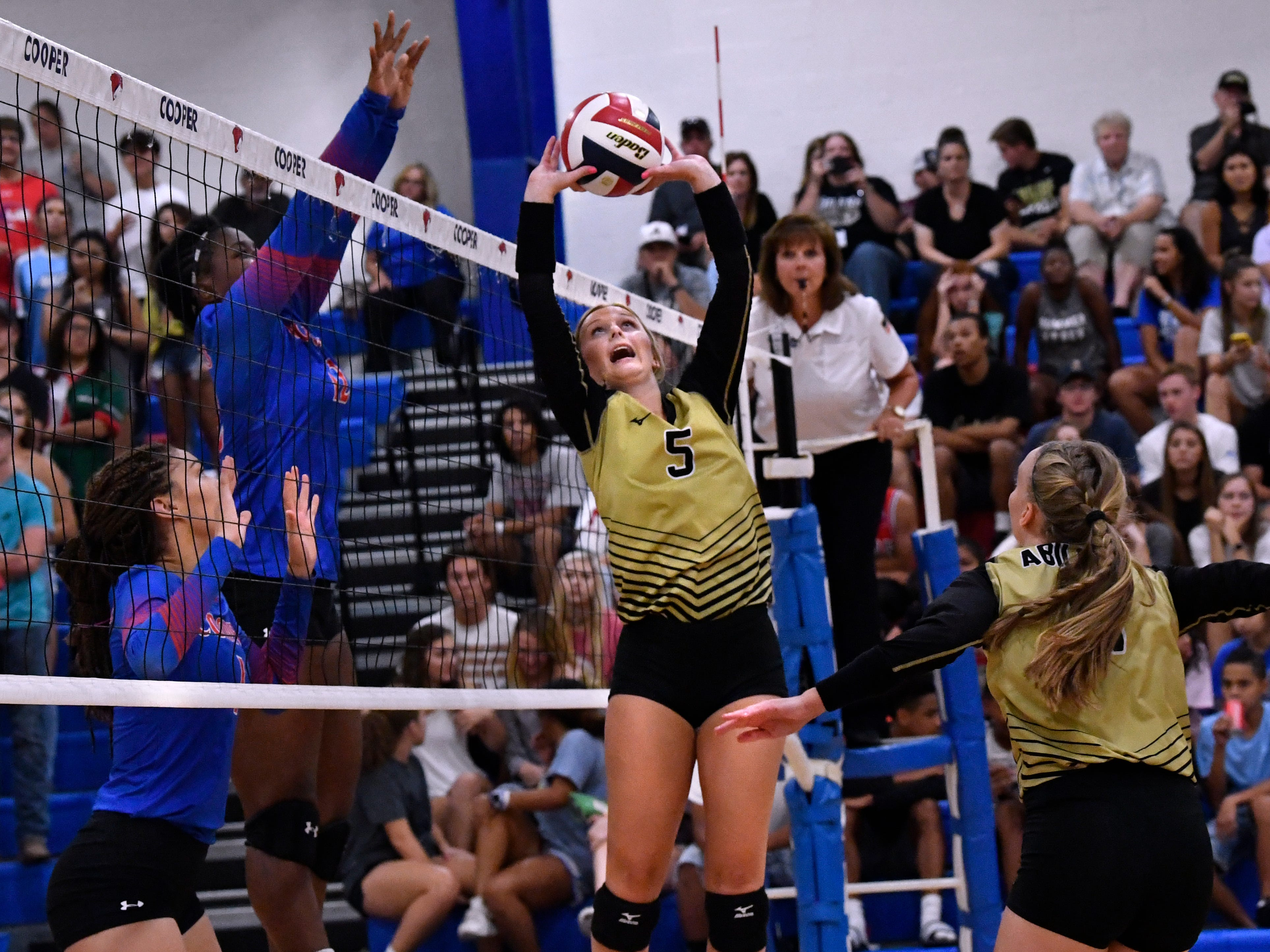 Abilene High's Allison Pierce sets the ball for teammate Sarah Cox. Abilene High won the crosstown volleyball game Tuesday August 7, 2018 against Cooper High in the best-of-five match, 25-21, 16-25, 25-20, 17-25, 15-7.