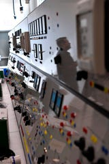 Richard Filut is reflected in the panel of a machine used to train students for work at an electrical substation Aug. 8.