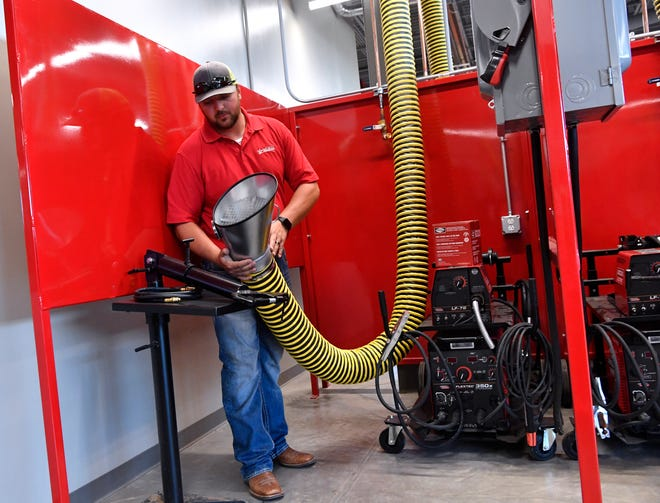 Greg Nicholas holds one of the exhaust hoses in the welding lab during a tour at Texas State Technical College Abilene Aug. 8. Classes begin Monday at the new built $12 million campus next to Abilene Regional Airport.