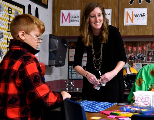 Kaitlin Hoermann, a third-grade teacher at Allie Ward Elementary School, helps Braylon Ramos (left) while talking with another student during class May 24.