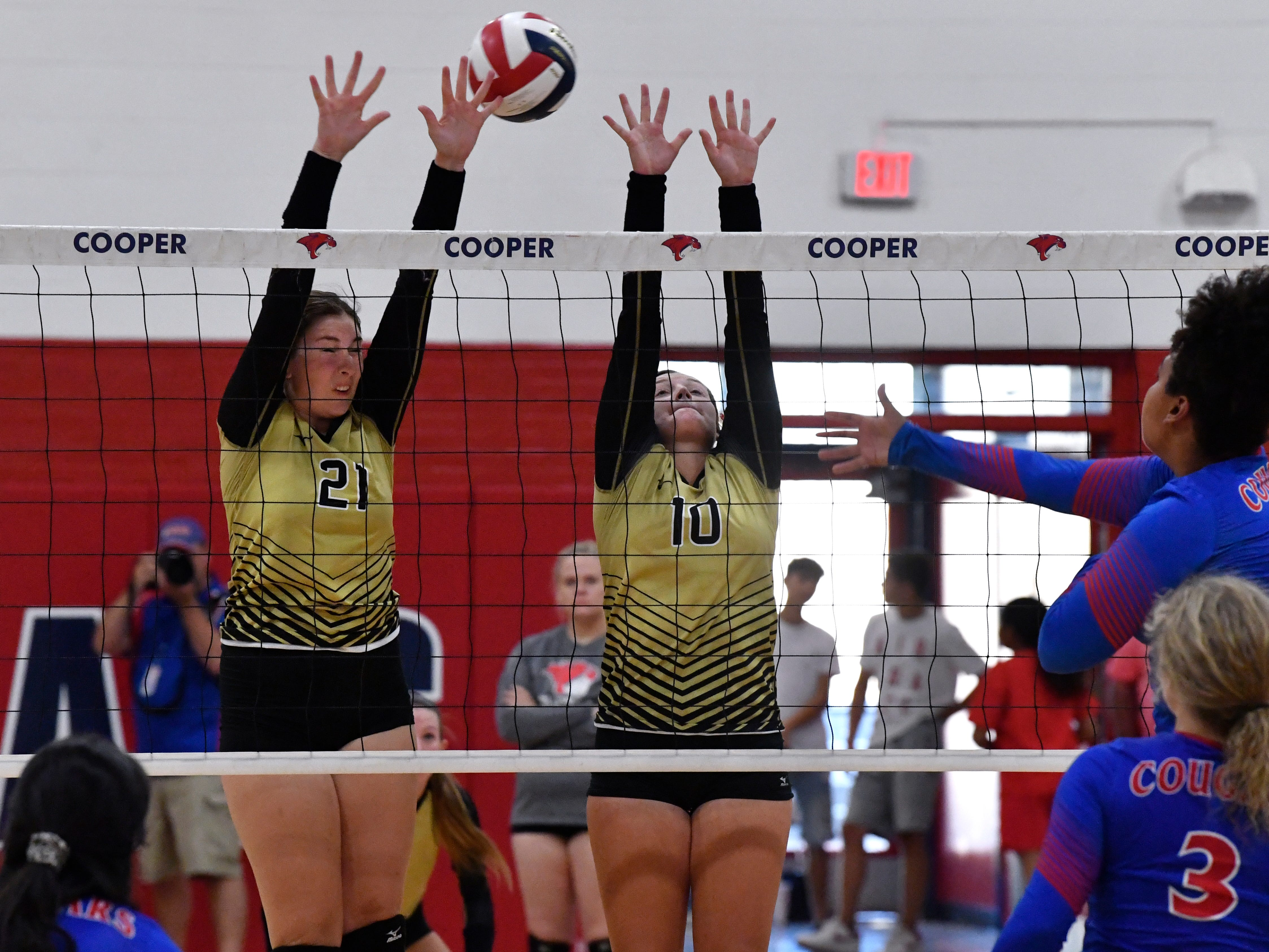 Abilene High's Sydne Lawler (left) and Saige McCray try to block a spike from Cooper's Jada Willis. Abilene High won the crosstown volleyball game Tuesday August 7, 2018 against Cooper High in the best-of-five match, 25-21, 16-25, 25-20, 17-25, 15-7.