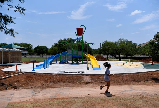 A jogger runs past the Sears Park splash pad Saturday. The city's final splash pad was planned to open Friday but is still in need of landscaping and concrete pathways.