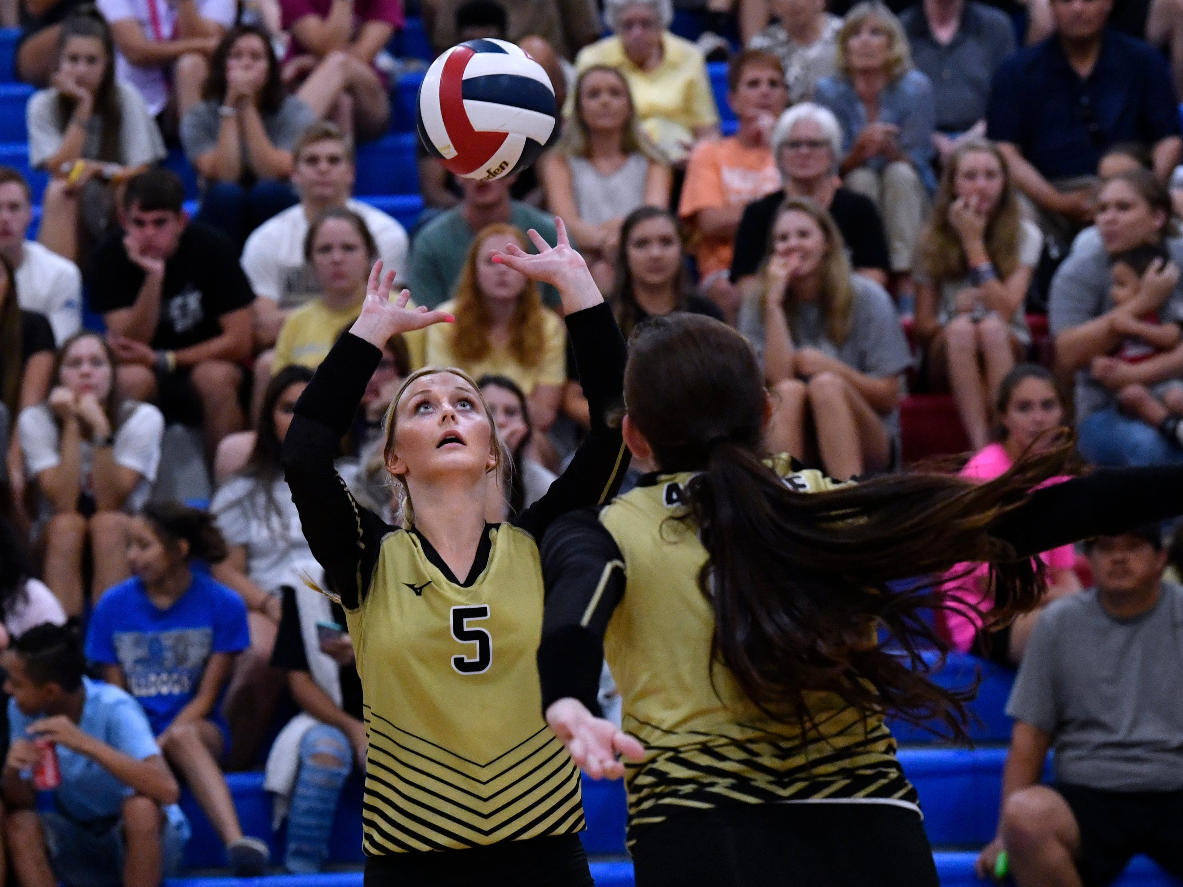 Abilene High's Allison Cooper sets the ball for Sydney Lawler. Abilene High won the crosstown volleyball game Tuesday August 7, 2018 against Cooper High in the best-of-five match, 25-21, 16-25, 25-20, 17-25, 15-7.