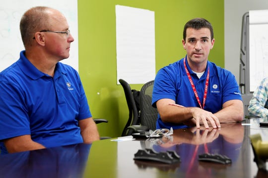 Ted Limbo, CMC technology lead, left, and Ryan Huth, GE Aviation plant manager, discuss the delivery of their 25,000th jet engine CMC shroud August 8, 2018, in Asheville.