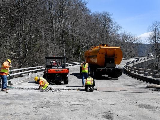 """Bryant's Land Development employees work on one of two bridge joints in the Linn Cove Viaduct in April The Blue Ridge Parkway has had several paving projects taking place this summer, including adding """"chip seal"""" on a section between Brevard Road to Milepost 413, south of Mount Pisgah."""