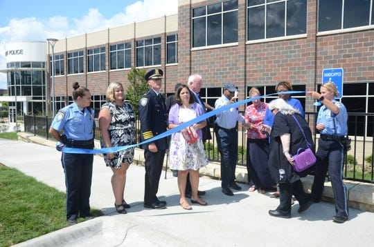 Commissioner Susan Baldwin ducks under the ribbon before the official opening of the building.