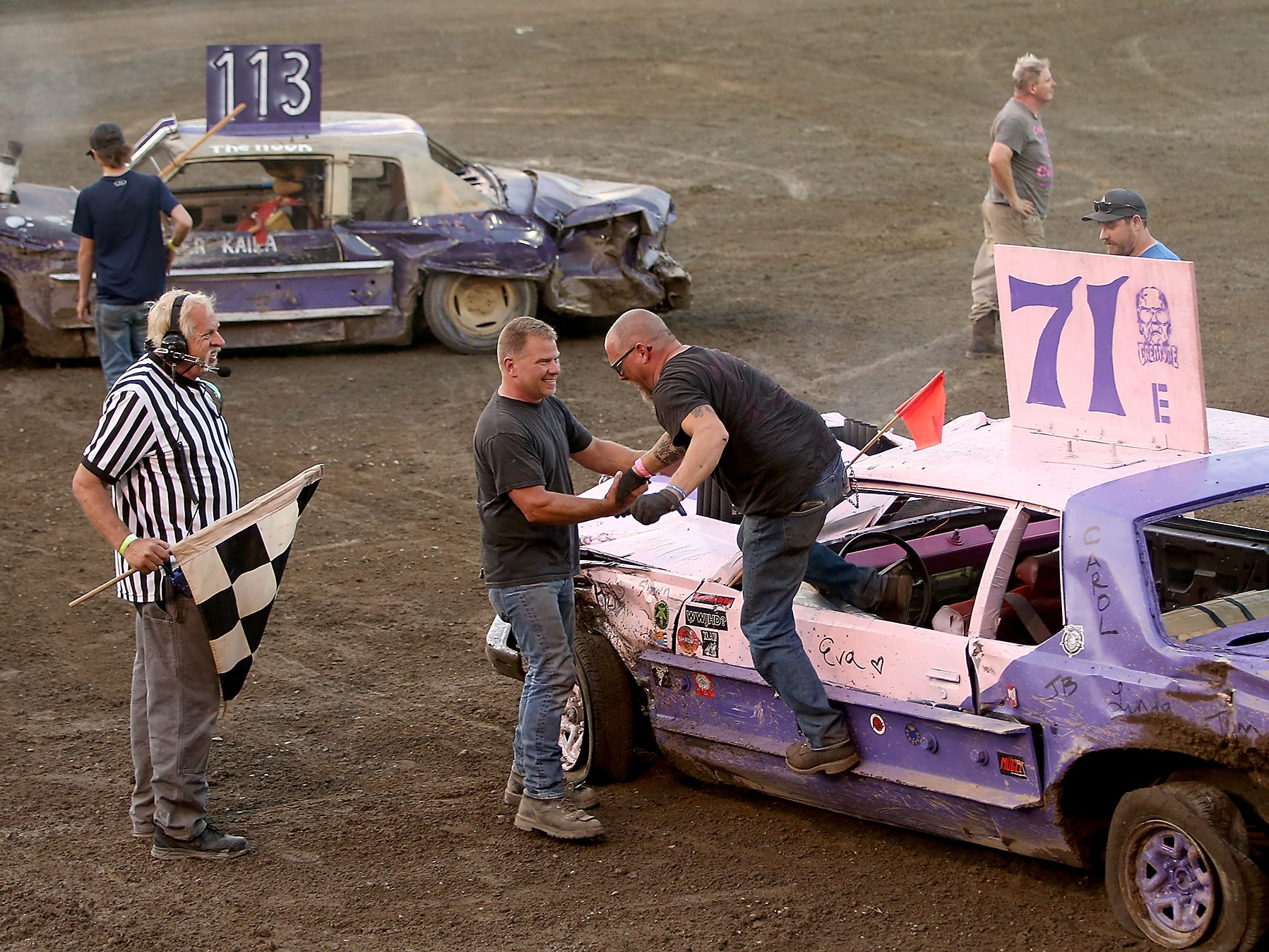 Drivers Dan Pieze (center) congratulates and gives a hand to finale winner Geof Higham (right) as he exits his car in the middle of Thunderbird Arena on Saturday, July 28, 2018.