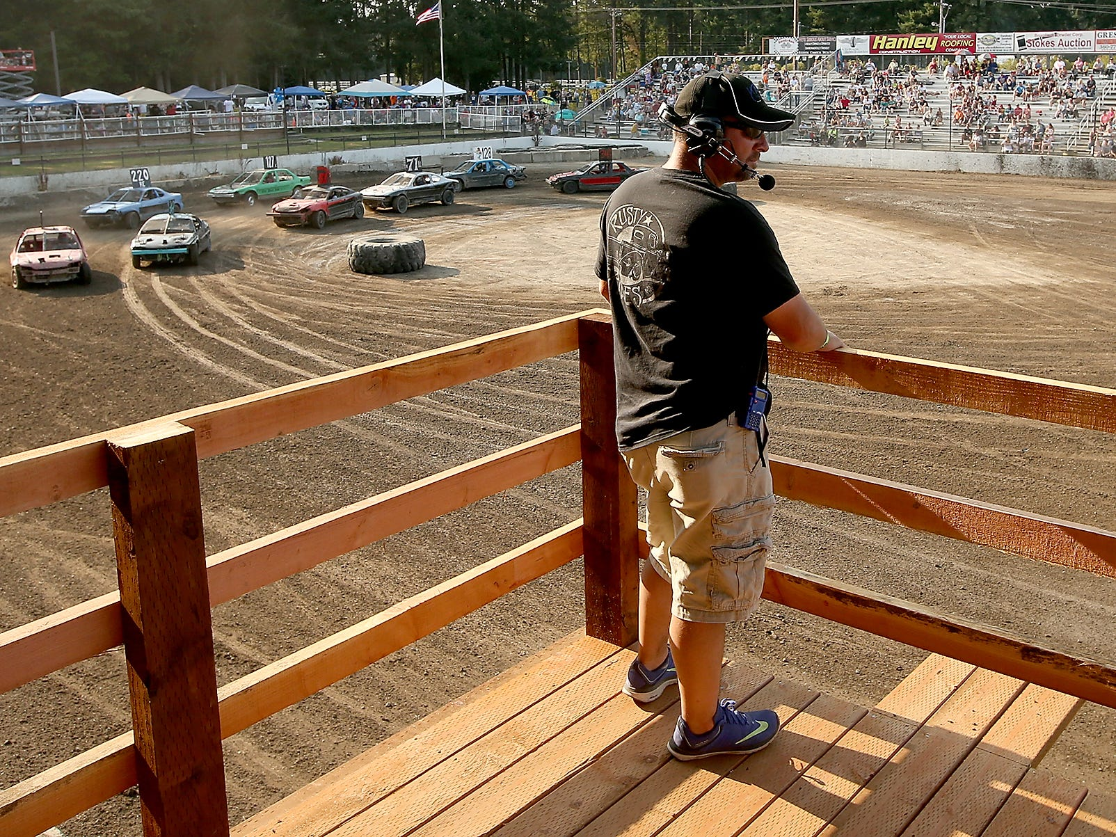 Head Judge Todd Williams keeps his eye on flagger Mike Stevenson as the cars ready for the start below during the Kitsap Destruction Derby on Saturday, July 28, 2018.